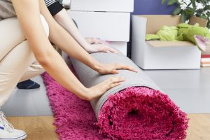People rolling a fuzzy pink carpet while packing